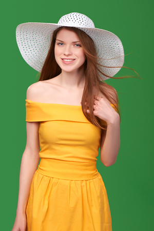 strapless dress: Closeup portrait of smiling pretty girl in yellow strapless summer dress and wide-brimmed straw hat with flying hair, over green background