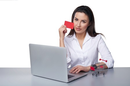 woman shopping cart: Online payment shopping concept. Business woman sitting at table with laptop, small empty shopping cart standing on table, holding empty credit card, isolated on white background