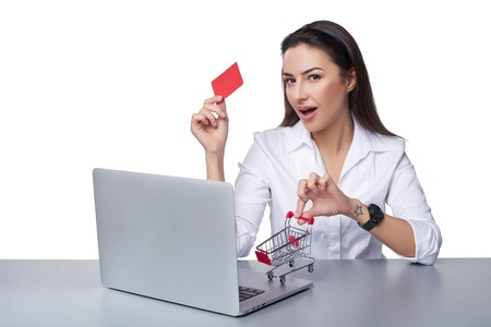 woman shopping cart: Online shopping concept. Playful business woman sitting at table with laptop with small empty shopping cart standing on table, holding empty credit card, isolated on white background