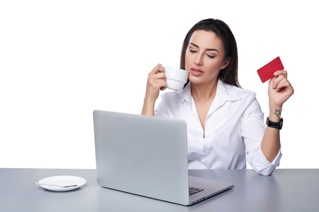 Online payment shopping concept. Confident business woman sitting at table with laptop, holding empty credit card going to pay online, drinking coffee, isolated on white background
