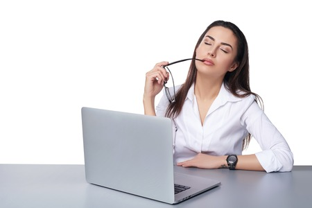 Tired business woman sitting at table with laptop relaxing with closed eyes, isolated on white background