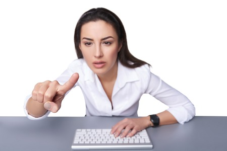 woman pointing: Portrait of a young business woman leaning against a keyboard and pointing at imaginary button, isolated on white. Shallow depth of field, focus on the finger.