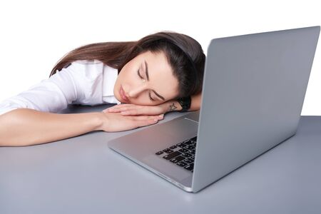 exploited: Young businesswoman asleep on her laptop at work Stock Photo