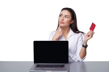 envisioning: Thinking business woman showing blank black laptop computer screen and holding blank credit card in hand looking away at blank copy space in thoughts, over white background