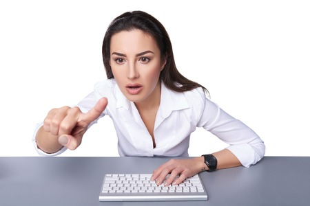 professionalism: Portrait of surprised young business woman leaning against a keyboard and pointing at imaginary button, isolated on white. Shallow depth of field, focus on the woman Stock Photo