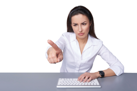 displeased: Portrait of displeased business woman with keyboard pointing at imaginary button on blank copy space, isolated on white. Shallow depth of field, focus on the finger