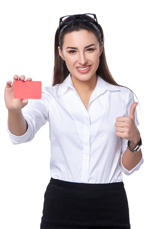 approving: Portrait of young smiling business woman showing credit card and showing approving sign, isolated on white background