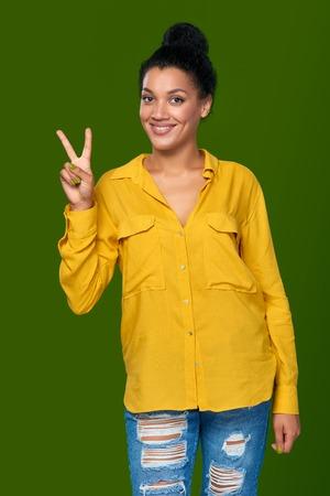 signo de paz: Feliz raza mixta afroamericana - mujer caucásica que muestra un dedo, la dirección de arriba Foto de archivo