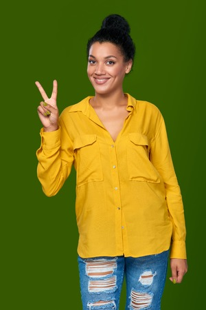 peace sign: Happy mixed race african american - caucasian woman showing one finger, directing up
