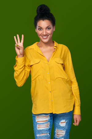 Hand counting - three fingers. Happy mixed race african american - caucasian woman showing one finger, directing up Stock Photo