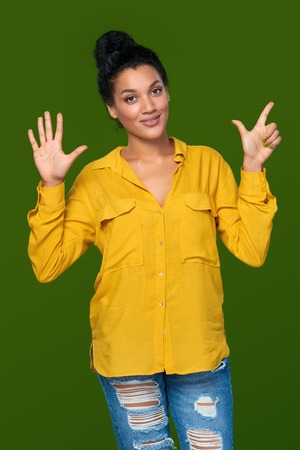 number seven: Hand counting - seven fingers. Happy mixed race african american - caucasian woman indicating the number seven with her fingers Stock Photo