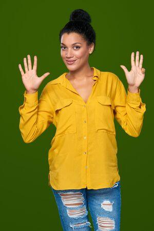 numero nueve: Cuenta de la mano - nueve dedos. Raza mixta afroamericana feliz - mujer cauc�sica que indica el n�mero nueve con sus dedos