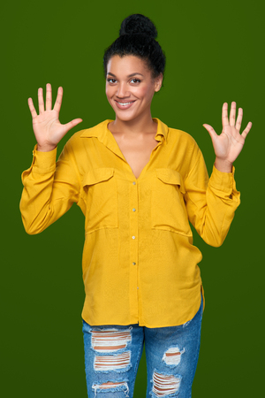 numero diez: Hand counting - ten fingers. Happy mixed race african american - caucasian woman indicating the number ten with her fingers