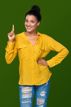 pointing finger up: Hand counting - one finger. Happy mixed race african american - caucasian woman showing one finger, directing up, idea concept