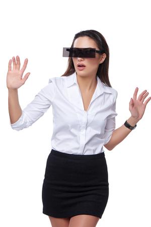 ojos vendados: Hermosa mujer de negocios con gafas futuristas caminando con las manos hacia adelante, sobre el fondo blanco