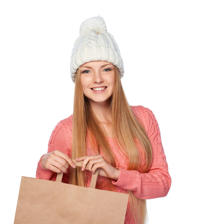 white hat: Winter shopping concept. Happy woman wearing knit hat and sweater sholding paper shopping bag with copy space, over white background Stock Photo