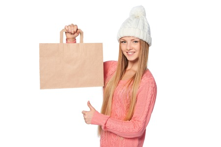 paper bag: Winter shopping concept. Happy woman wearing knit hat and sweater holding paper shopping bag with copy space and gesturing thumb up, over white background