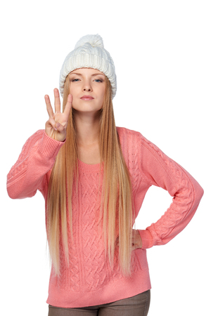 three: Hand counting - three fingers. Portrait of woman on white background wearing woolen hat and sweate showing three fingers