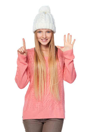 six girls: Portrait of woman on white background wearing woolen hat and sweater showing six fingers Stock Photo