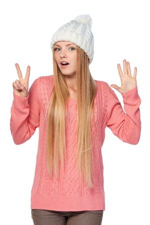 dedo: Retrato de la mujer en el fondo blanco con el sombrero de lana y un su�ter mostrando siete dedos
