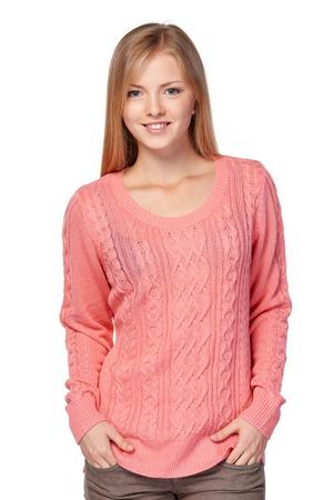 ホワイト スタジオの背景にさりげなくピンクのニット セーター立っての素敵なブロンド女性がポケットに手します。