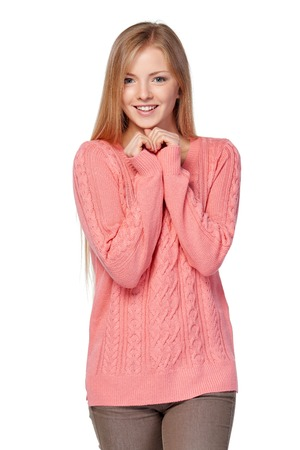 Lovely blond female in pink knit sweater standing playful over white studio background Archivio Fotografico