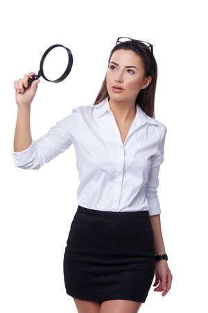 looking through: Business search concept. Concentrated business woman looking through magnifying glass Stock Photo