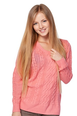 fashion clothes: Lovely blond female in pink knit sweater standing casually smiling over white studio background