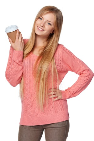 women coffee: Lovely blond female in pink knit sweater standing casually holding a drink in disposable paper cup over white studio background Stock Photo