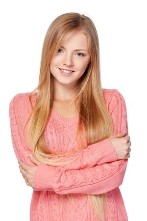 folded hands: Lovely blond female in pink knit sweater standing with folded hands smiling over white studio background