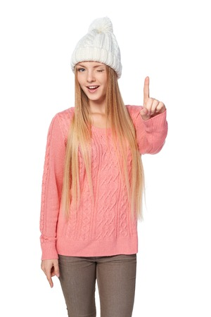 white playful: Idea concept. Portrait of playful alluring woman on white background wearing woven hat and sweater with finger up, winking at you