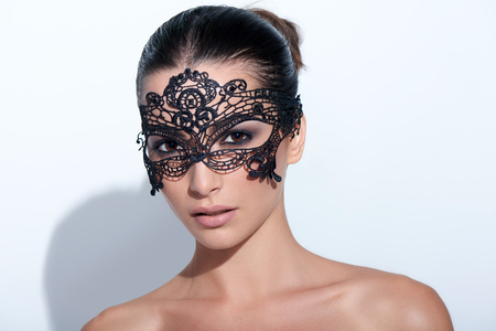 Closeup portrait of beautiful woman with evening smokey makeup and black lace mask over her eyes Foto de archivo
