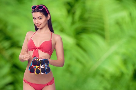 pink bikini: Smiling woman in pink bikini holding many colourful sunglasses, over green nature background