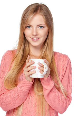 hot drink: Lovely blond female in pink knit sweater standing casually holding a hot drink in a cup over white studio background Stock Photo