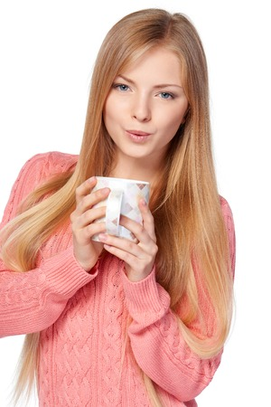 femme blonde: Lovely blond female in pink knit sweater standing casually holding a hot drink in a cup, blowing to cool a drink, over white studio background
