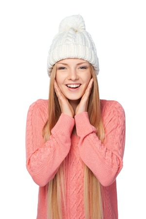 sweater girl: Surprised female in pink knit sweater with hands on cheeks over white studio background