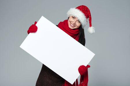 wearing santa hat: Holidays, Christmas. Portrait of smiling woman wearing Santa hat showing whiteboard banner over gray background Stock Photo