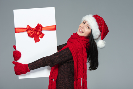 excited woman: Christmas, Xmas, winter gift concept. Happy excited woman wearing Santa hat carrying gift box with red bow, isolated on grey