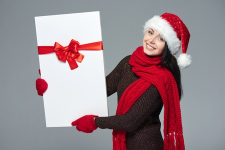 christmas woman: Christmas, Xmas, winter gift concept. Happy excited woman wearing Santa hat carrying gift box with red bow, isolated on grey