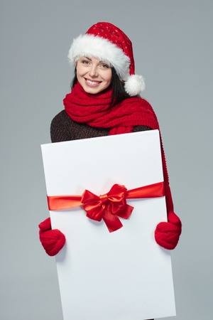 carry on: Christmas, Xmas, winter gift concept. Happy excited woman wearing Santa hat carrying gift box with red bow, isolated on grey