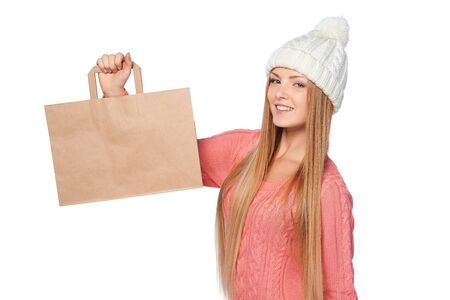 paper bag: Winter shopping concept. Happy woman wearing knit hat and sweater sholding paper shopping bag with copy space, over white background Stock Photo