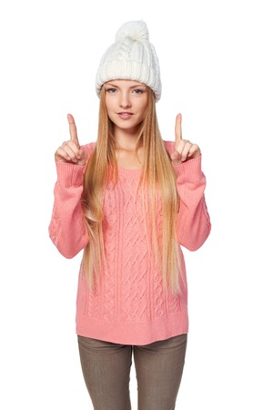 white playful: Idea concept. Portrait of playful alluring woman on white background wearing woven hat and sweater pointing two fingers up