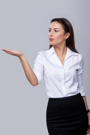 showing: Beautiful business woman blowing on palm, over grey background