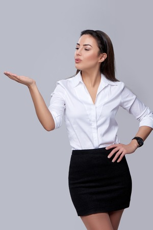 mouth kiss mouth: Beautiful business woman blowing on palm, looking at copy space on her palm, over grey background