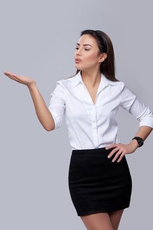 boca abierta: Hermosa mujer de negocios que sopla en la palma, mirando copia espacio en su palma, sobre fondo gris Foto de archivo