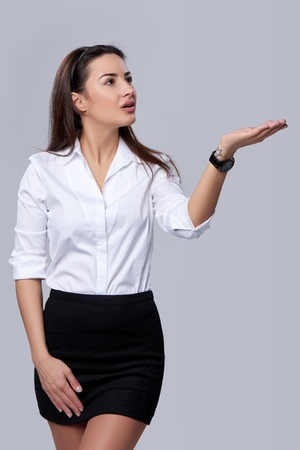 executive woman: Beautiful business woman blowing on palm, looking far away upwards, over grey background Stock Photo