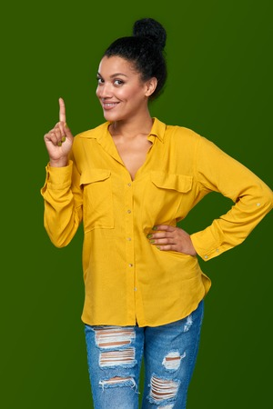 excited woman: Idea. Happy mixed race african american - caucasian woman pointing her finger up