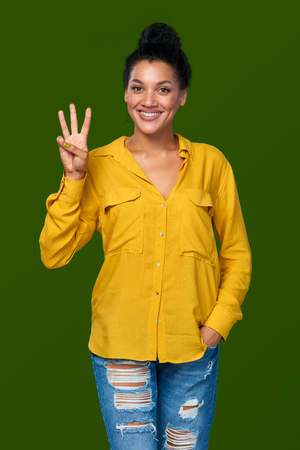 tres dedos: Hand counting - three fingers. Happy mixed race african american - caucasian woman showing three fingers