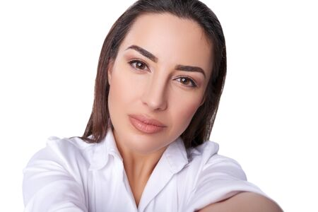 young woman face: Closeup of serious woman wearing white shirt making selfie photo on isolated white background and looking at camera