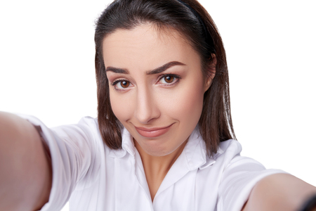 Closeup of beautiful business woman making a funny face for the selfie photo